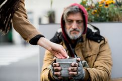 Unrecognizable woman giving money to homeless beggar man sitting in city. royalty free stock photos