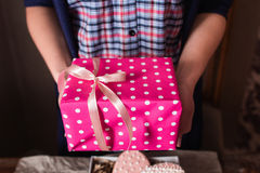 Unrecognizable woman holding pink gift box Stock Images