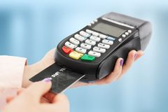 Unrecognizable woman holds swiping machine and credit card, pays for purchase, uses bank terminal in shop, isolated over blue back. Ground. POS terminal in store Stock Photos