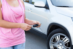 Unrecognizable woman with ignition key standing near own vehicle Stock Images
