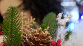 Unrecognizable woman looks out through Christmas baubles. Unrecognizable young curly woman looks out through Christmas baubles, toys and decorations during the stock footage