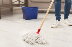 Unrecognizable woman with mop ready to clean floor. Unrecognizable woman with cleaning equipment ready to clean house. Cropped girl holding mop, professional Stock Photo