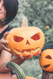 Unrecognizable woman near pumpkin is holding a jack-o-lantern in her hands. Halloween. Decoration for party. Close up. Toned photo Stock Images