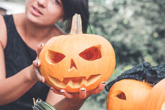 Unrecognizable woman near pumpkin is holding a jack-o-lantern in her hands. Halloween. Decoration for party. Close up. Toned photo Stock Image