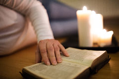 Unrecognizable woman reading Bible. Burning candles next to her. Stock Image