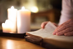 Unrecognizable woman reading Bible. Burning candles next to her. Stock Photography
