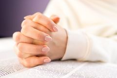 Unrecognizable woman reading big book - Holy Bible and praying. Christian studying scripture. Student in the college. Library preparing for exams. Learning royalty free stock image