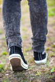Unrecognizable woman in rubber shoes stepping on the footpath, rear view, vertical Stock Images