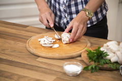 Unrecognizable woman slicing mushrooms in the kitchen. Stock Photos