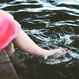 Unrecognizable woman splashing water with bare feet. Unrecognizable girl or young woman sitting on jetty by lake splashing water with bare feet stock images