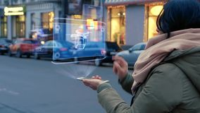Unrecognizable woman standing on the street interacts HUD hologram with delivery drone. Girl in warm clothes with a scarf uses technology of the future mobile stock video