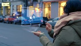 Unrecognizable woman standing on the street interacts HUD hologram with pills. Girl in warm clothes with a scarf uses technology of the future mobile screen on stock footage