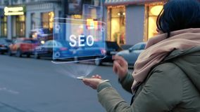 Unrecognizable woman standing on the street interacts HUD hologram with text SEO. Girl in warm clothes with a scarf uses technology of the future mobile screen stock footage