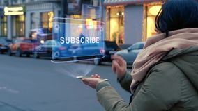 Unrecognizable woman standing on the street interacts HUD hologram with text Subscribe. Girl in warm clothes with a scarf uses technology of the future mobile stock footage