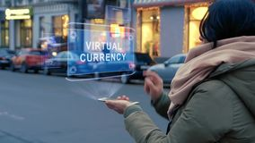 Unrecognizable woman standing on the street interacts HUD hologram with text Virtual currency. Girl in warm clothes with a scarf uses technology of the future stock video