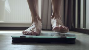 Unrecognizable woman stands on floor scale in the bedroom. Bottom view on female legs stock footage