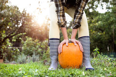 Unrecognizable woman in striped rubber boots holding orange pump Stock Photos