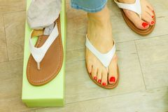 Unrecognizable woman trying on flip flops. Unrecognizable woman trying on new flip flops in shop buying and choosing best footwear stock photography