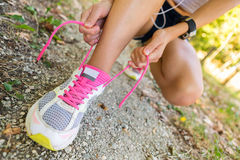 Unrecognizable woman tying shoelaces in the City park. Stock Images