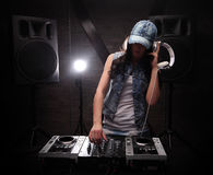 Unrecognizable woman with white headphones playing music on mixe. Young woman dj in headphones playing music on mixer on table Royalty Free Stock Photos