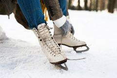 Unrecognizable woman in winter clothes putting on old ice skates. Close up. Snowy winter nature Stock Photo