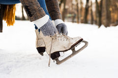Unrecognizable woman in winter clothes putting on old ice skates Stock Photos