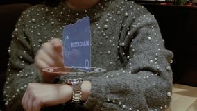 Woman uses hologram watch with text Blockchain. Unrecognizable woman working with HUD hologram of a smart watch with text Blockchain. Female hands with future stock video footage