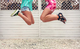 Unrecognizable women jumping over garden fence background Royalty Free Stock Photo