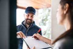 Woman receiving parcel from delivery man at the door. Unrecognizable women receiving parcel from delivery men at the door - courier service concept Royalty Free Stock Image