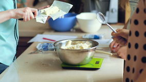 Unrecognizable women slices butter into a bowl stock video