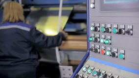 Unrecognizable worker at a modern industrial equipment operating with metal sheet. Control panel display. Slider shoot. Unrecognizable worker at a modern stock footage