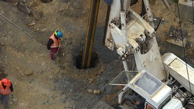 Unrecognizable workers with hydraulic hammer drilling machine at. Aerial view of unrecognizable workers with hydraulic hammer drilling machine creating stock footage