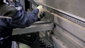 Unrecognizable workers operating bending equipment, bending metall sheets at a industrial factory. Metal bending machine. Unrecognizable worker operating bend stock footage
