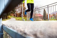 Young athlete running in park in colorful autumn nature. Unrecognizable young athlete in yellow jacket running outside by the lake. Trail runner training for Stock Images