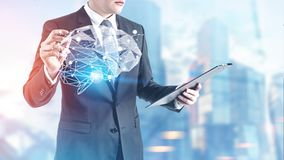 Businessman with a glowing marker, brain. Unrecognizable young businessman is looking at his clipboard and holding a glowing marker. A brain hologram against a stock photos