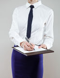 Unrecognizable young businesswoman  holding documents and a pen Stock Image