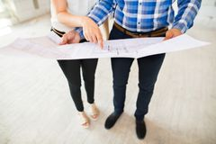 Unrecognizable young couple at the construction site. A men and women looking at plans of the new house, discussing issues at the construction site Royalty Free Stock Photo