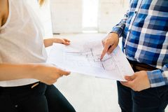 Unrecognizable young couple at the construction site. A men and women looking at plans of the new house, discussing issues at the construction site Stock Photo