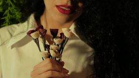 Unrecognizable woman holding artificial flowers. Unrecognizable young curly woman in white with bright red lipstick holding a bouquet of artificial flowers stock footage