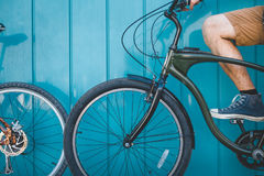 Unrecognizable Young Cyclist Sitting With A Bicycle Along A Blue Wall Background Daily Lifestyle Urban Resting Concept. A young male traveler stands along a blue royalty free stock image