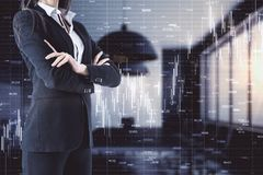 Trade and invest concept. Unrecognizable young european businesswoman with folded arms standing in blurry office interior with forex chart. Trade and invest stock image