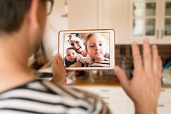 Father at home with tablet, video chatting with his family. Unrecognizable young father at home holding a tablet, video chatting with wife and children royalty free stock photo