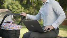 Unrecognizable young father using laptop and rocking baby stroller in summer park outdoors. Busy Caucasian man taking