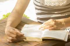 Unrecognizable young female reading a book outdoors. Hands of young female on the opened book. Unrecognizable person. She is wearing striped dress and sitting in Stock Photo