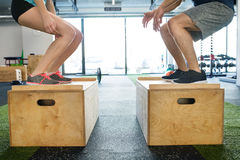 Unrecognizable young fit couple in gym doing box jumps. Royalty Free Stock Image