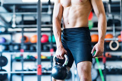Unrecognizable young fit man in gym exercising with kettlebell. Stock Image