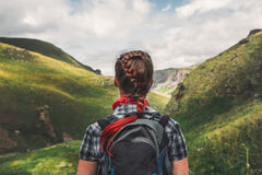 Unrecognizable traveler woman with backpack enjoying view of summer mountains, rear view. Unrecognizable young girl with red hair and a backpack is enjoying the Stock Photography