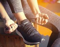 Unrecognizable young girl runner tying her shoelaces. Studio sho Stock Photo