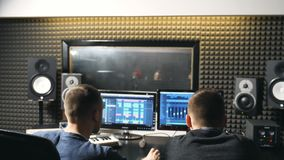 Unrecognizable young male audio editor and music producer working in the recording studio. Sound engineer creation a new