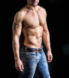 Unrecognizable young man with naked muscular torso. Wearing jeans, isolated on black background royalty free stock photos